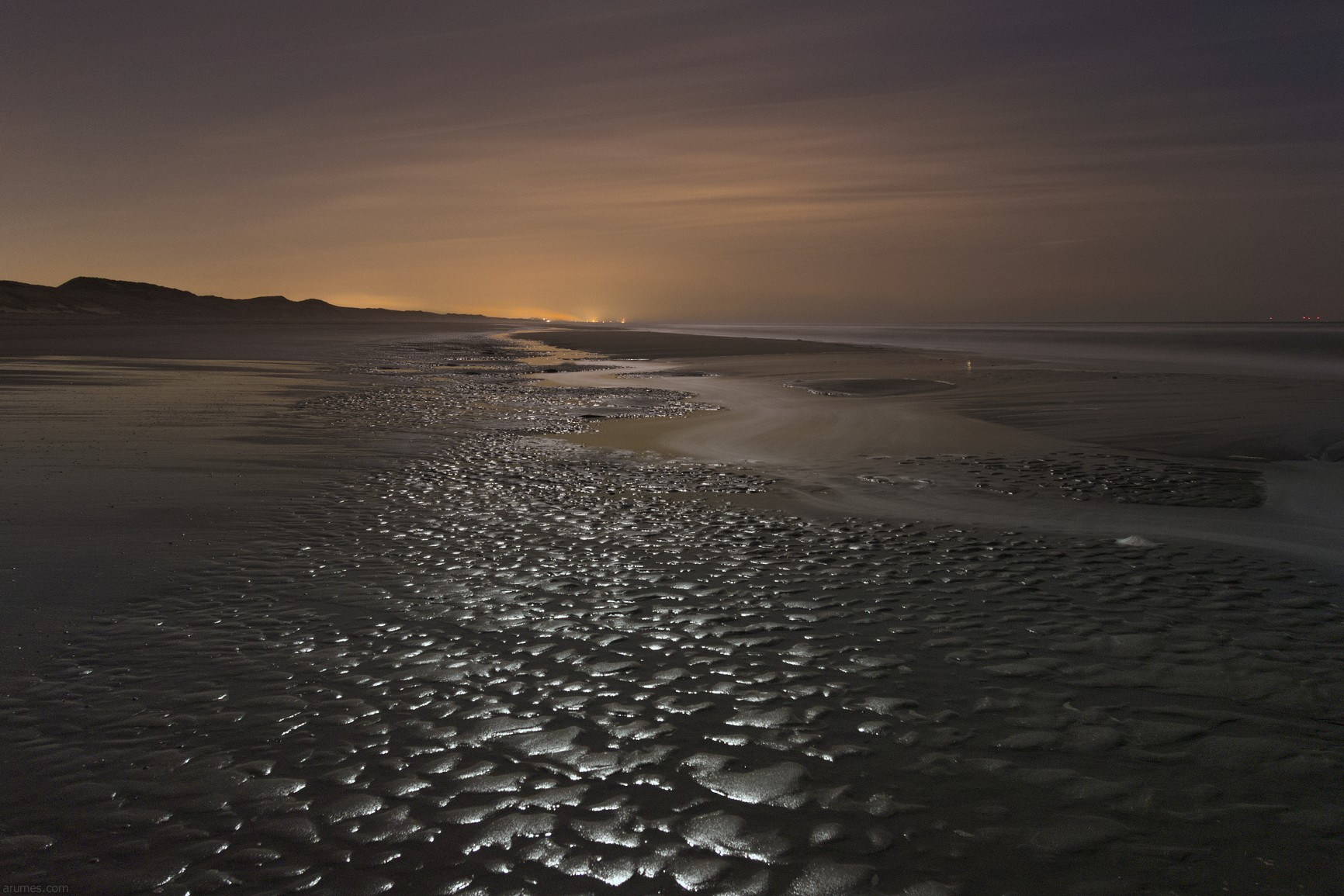 Beach wih incoming tide, artificial light on clouds and moon reflecting in wet sand